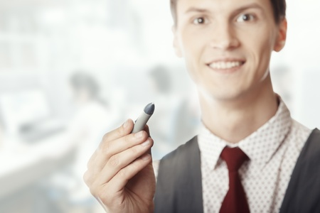 Smiling businessman holding a pen at his office Stock Photo - 14737267
