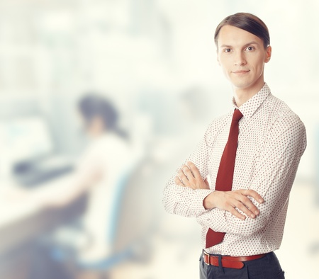 Young businessman stands in defocused office. Color photo Stock Photo - 14737276