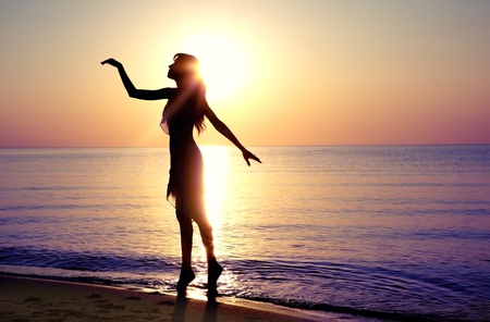 Silhouette of the woman dancing at the beach during beautiful sunrise. Natural light and darkness photo