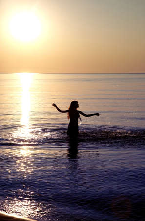 Silhouette of the woman playing with water during sunset. Natural darkness and colors photo