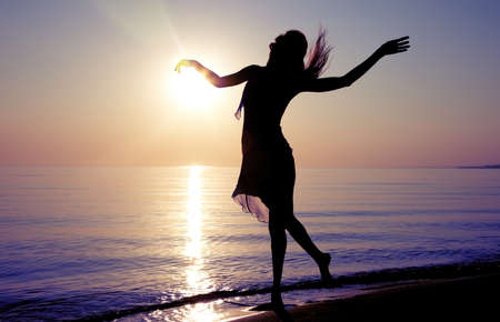 Silhouette of the woman dancing at the beach during beautiful sunrise. Natural light and darkness Stock Photo - 14797534
