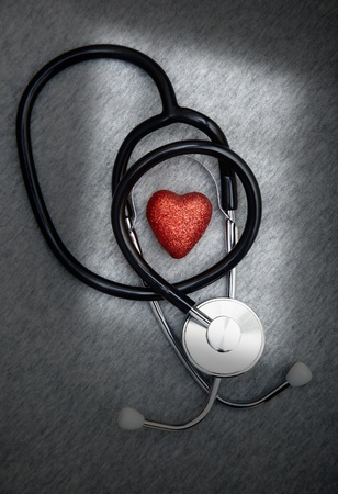 cardiosurgery: Stethoscope and heart symbol on a dark table with shadows