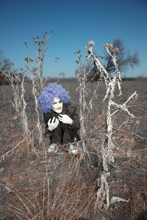 Crazy evil clown sitting outdoors photo