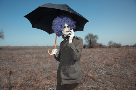 Sad clown outdoors hodling black umbrella photo