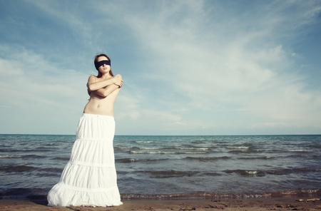 Lady with blindfold stands at the beach Stock Photo