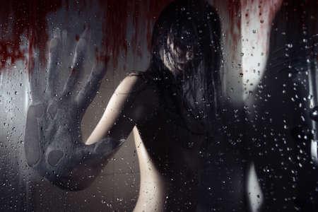 loup garou: Loup-garou dans la salle de bain sombre toucher humide verre sanglante par sa grosse main avec des clous pointus. Obscurité naturelle. Couleurs artistiques et le grain ajouté Banque d'images