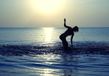 Silhouette of the happy woman playing with water at summer beach photo
