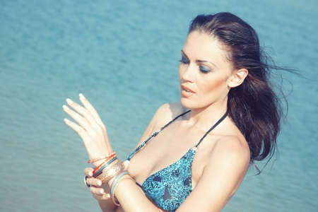Attractive lady with bracelet at summer beach photo
