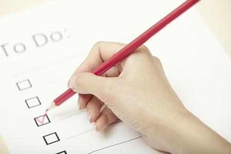 Human hand writing on a checklist document photo