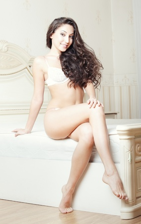 Attractive lady sitting and pamepring in bedroom photo