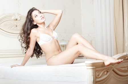 Attractive lady lying and pamepring in bedroom photo