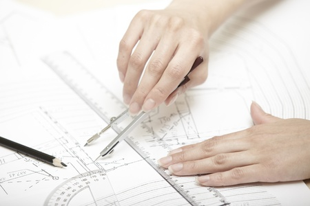 protractor: Hands of engineer working on a construction plan