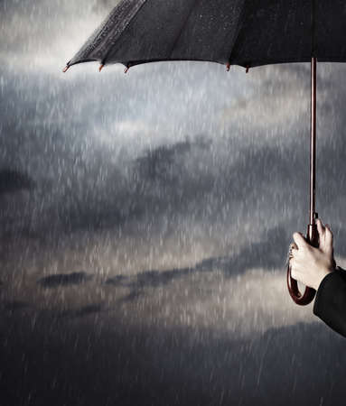 rainstorm: Human hands holding big black umbrella under the heavy rain