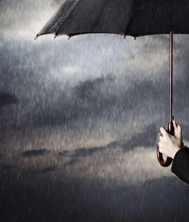 lluvia paraguas: Las manos humanas sosteniendo paraguas negro grande bajo la lluvia Foto de archivo