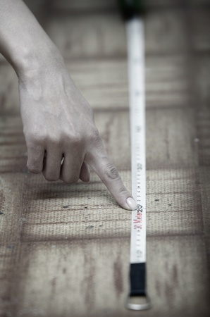 Human hands using measuring tape on a wooden surface photo