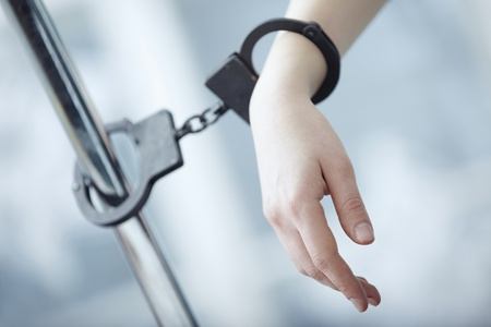 Human hand bounded to the metal pole by handcuffs Stock Photo - 16907857