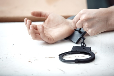 Human hands opening handcuffs.  photo