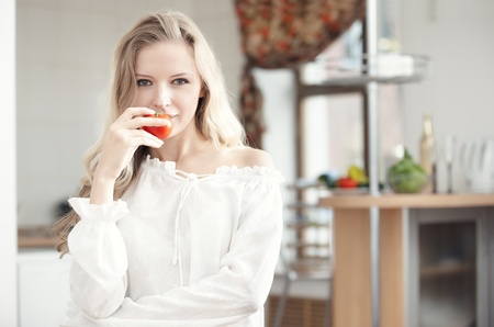 Blond lady with ripe tomato at the kitchen Stock Photo
