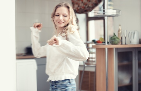 everyday people: Smiling blond lady dancing at the kitchen Stock Photo