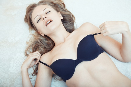 Blond lady laying on the bed and taking pleasure Stock Photo