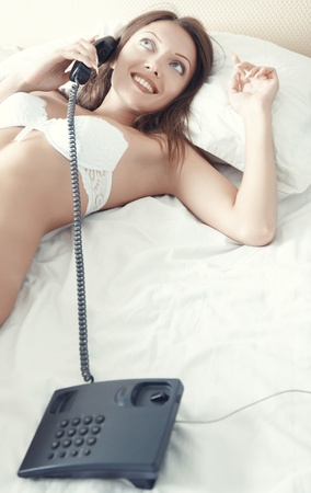 Lady in white camisole talking via telephone Stock Photo - 17540174