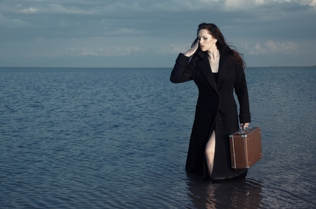 Woman in black coat standing in the sea with luggage photo