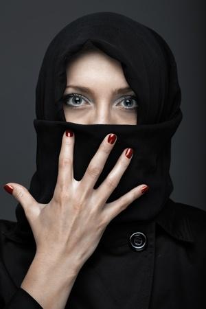 Woman in black ninja dress with manicure photo