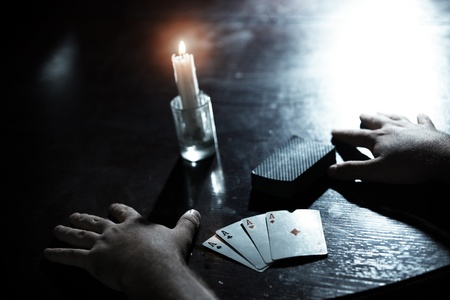 fortunetelling: Human hands on a dark table with pack of cards and flaming candle