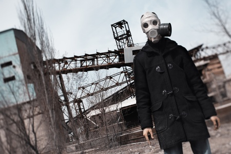 doomsday: Man in gas mask standing at the factory after doomsday Stock Photo
