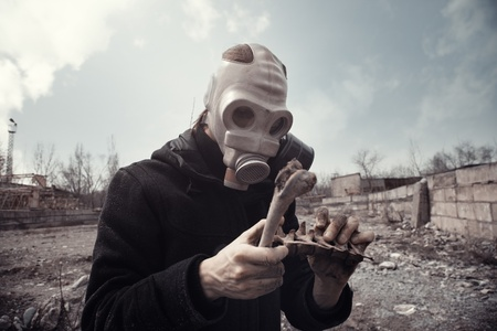doomsday: Man in gas mask holding residual bones after doomsday