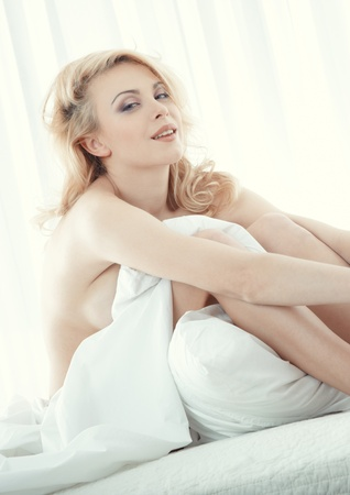 Attractive smiling lady sitting on the bed photo