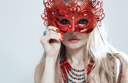 Blond lady in jewelry holding masquerade mask photo