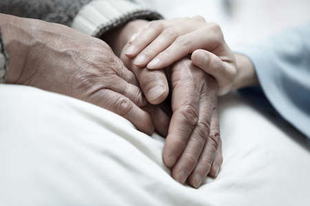 life support: Hand of woman touching senior man in clinic Stock Photo