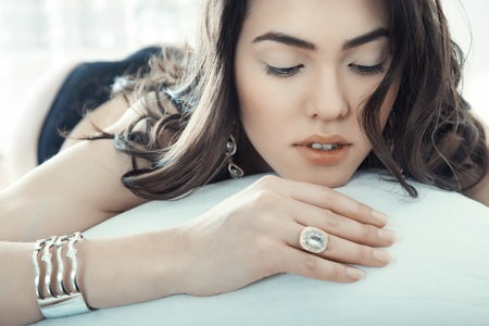 diamond earrings: Brunette lady with jewelry laying on the bed Stock Photo