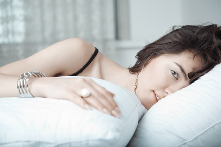 armlet: Brunette lady with jewelry laying on the bed Stock Photo