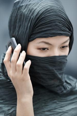 Muslim lady in hijab talking via cell phone photo