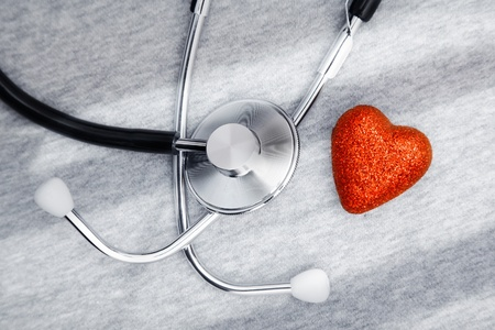 cardiosurgery: Stethoscope and heart symbol on a table with shadows Stock Photo