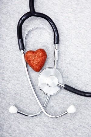 cardiosurgery: Medical stethoscope and heart on a blue textured background