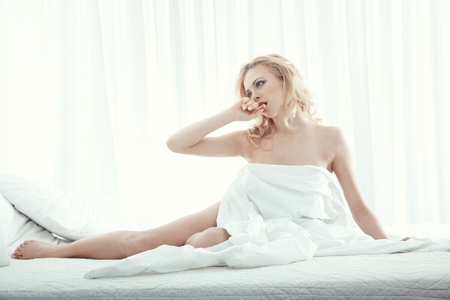 Happy blond lady indoors sits in the bedroom photo