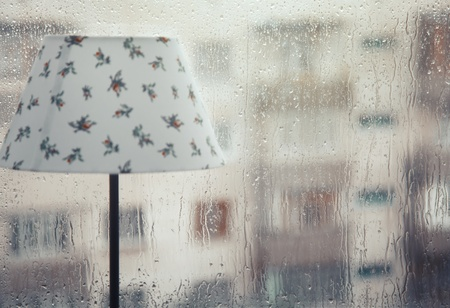 rainfall: Table lamp at the wet window and rainfall behind the glass