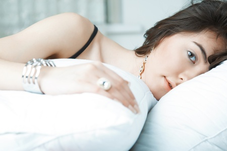 Brunette lady with jewelry laying on the bed Stock Photo - 22086033