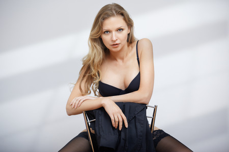 Sensual blond lady in lingerie sitting on the chair photo