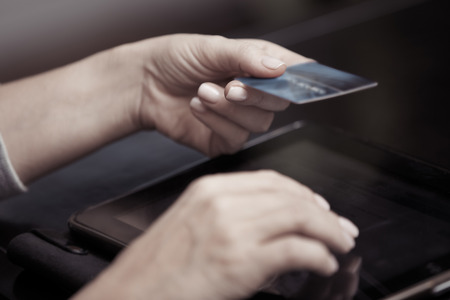 Woman hands holding credit card and tablet computer photo