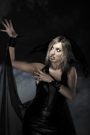 nightmarish: Woman in black witch dress for Halloween. Studio shot
