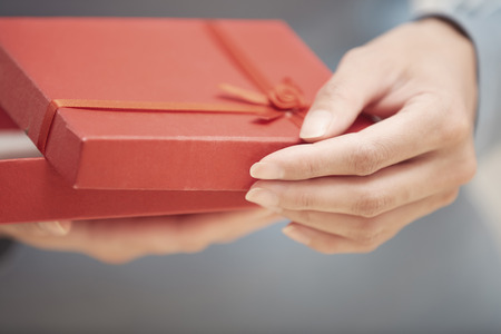 red gift box: Hands of woman opening red gift box Stock Photo