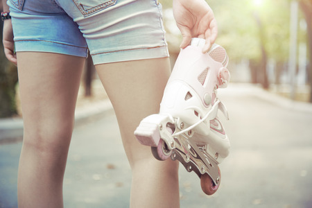 safety boots: Teenager holding roller skates in park. Horizontal photo