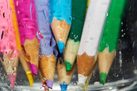variability: Color pencils behind the wet glass. Close-up photo Stock Photo