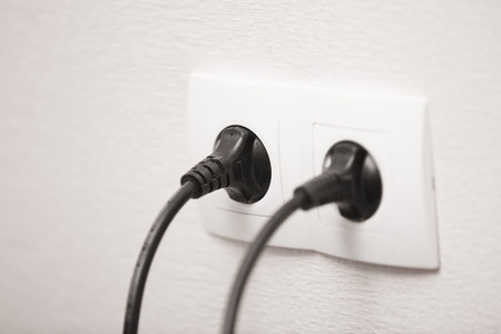 Close-up view of electric outlets with power cables photo