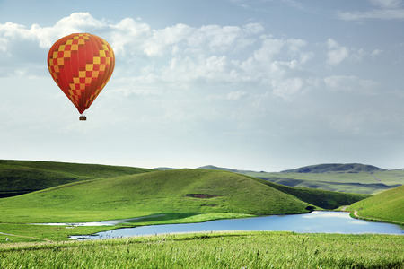 air transport: Air balloon flying over the meadows with lake Stock Photo