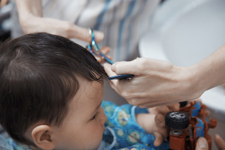 haircutter: Hands of hairdresser combing baby hair